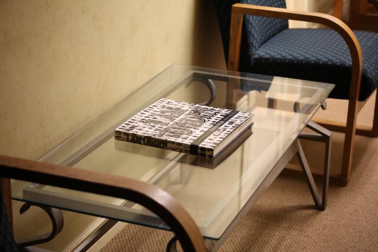 Sklenený stolík, knižka položená na sklenenom stolíku