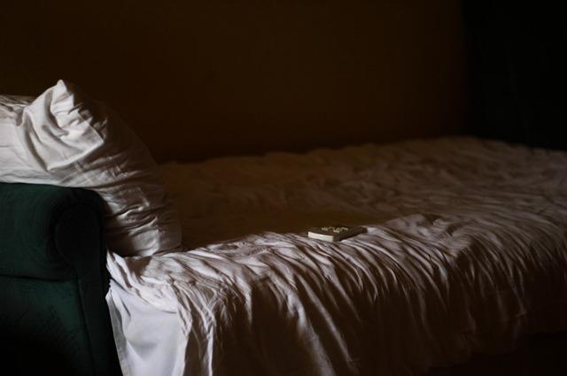 Tmavá izba s posteľou, na ktorej je vankúš, pokrčená obliečka a ovládač.jpg