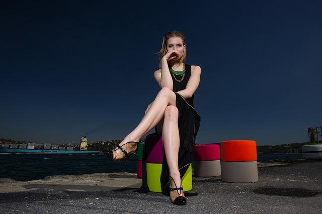 Žena v čiernych šatách sedí s preloženými nohami.jpg