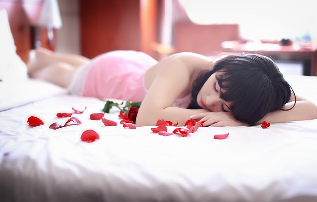 Žena leží na posteli, ruža, bielizeň