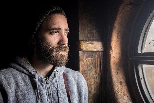 Muž s bradou sa pozerá von oknom a tvár sa smutne